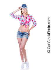 Funky beauty. Full length of beautiful young woman in funky wear adjusting her hat and looking at camera while standing against white background