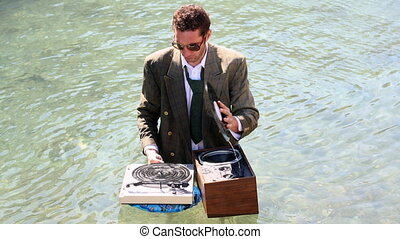funky dj in a suit plays in the sea