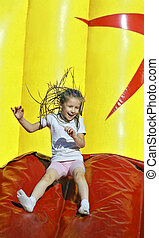 Funky fun in a summer park - Girl with inflatable slides...