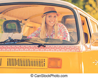 Funky girl in retro car. Happy young woman smiling at camera while looking through the vehicle window