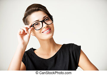 Funky style beauty. Beautiful young short hair woman adjusting her glasses and smiling