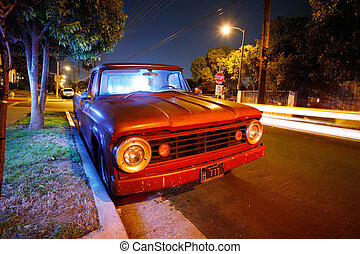 Funky vintage American pickup truck at night on a suburb street of Los Angeles, California, USA.