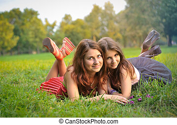 Funny 2 women lie on the grass