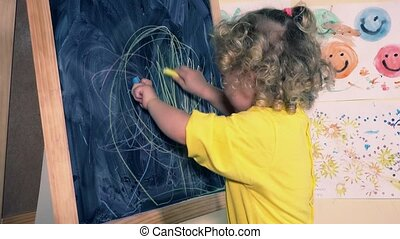 funny 2 years old child girl drawing with chalk at blackboard