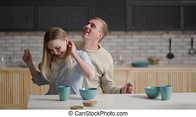 Funny active young couple in love dancing in kitchen. Cheery wife in dress hold her lively husband hand, cheerful family listen music enjoy carefree weekend at new modern warm home. Fun, hobby concept. High quality 4k footage
