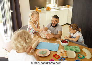 Delighted positive children having fun in the kitchen