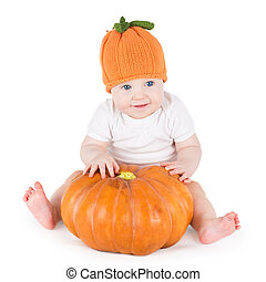 Funny adorable little baby playing with a big pumpkin wearing a