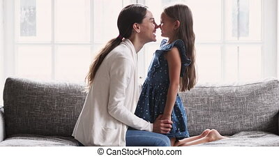 Funny affectionate mum and cute daughter touching noses playing together