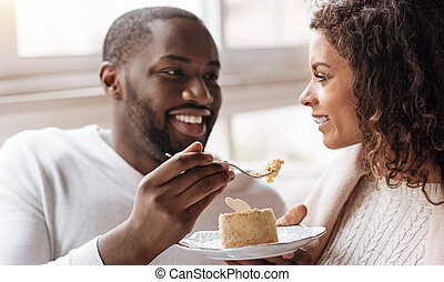 Funny African American couple enjoying the dessert in the cafe