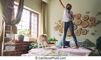 Funny African American girl is having fun listening to music, jumping and dancing on bed, singing in hair dryer with beautiful shiba inu dog walking on bed.