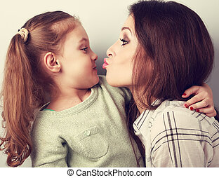 Funny amusing young mother wanting to kiss her comical grimacing daughter. Toned closeup portrait