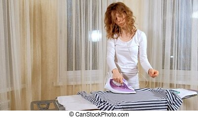 Funny and beautiful woman ironing clothes and dancing at...