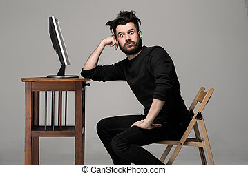 Funny and crazy man using a computer on gray background. ...