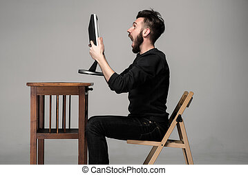 Funny and crazy man using a computer on gray background. man...
