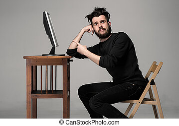 Funny and crazy man using a computer on gray background....