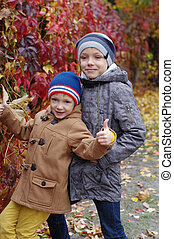 Funny and happy children are played against the background of autumn yellow leaves