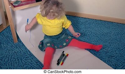 Funny artist child painting with pencil on paper sitting on floor