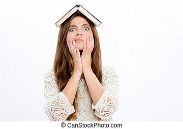 Funny astonished cute girl with opened book on her head