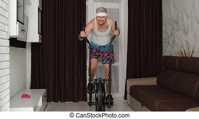 Funny Caucasian athlete sportsman guy couch on orbitrek in living room. Stylish hipster man blogger trainer recording sport fitness cardio online vlog at home. Sportive humor. Joke, comical, parody