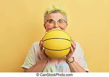 funny awsome old woman with dyed hair having fun with a basket ball