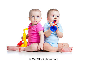 Funny babies girl and boy playing musical toys. Isolated on white background