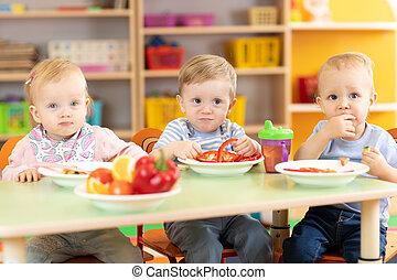 babies group eating vegetables in kindergarten dinning room