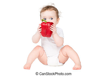 Funny baby biting on a big red paprika, isolated on white