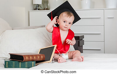 Funny baby boy in black graduation cap holding book