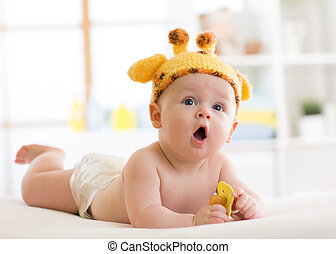 Funny baby boy in giraffe hat lying on his belly in nursery. Little kid lies on bed with opened mouth and holds soother in hands