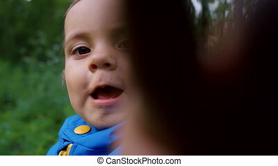 Funny baby boy looks into camera lens and then with interest begins to climb into frame with his hands. Knock knock, who is there. Green forest background. Family, love, child concept
