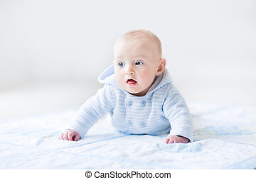 Funny baby boy playing on a bue blanket