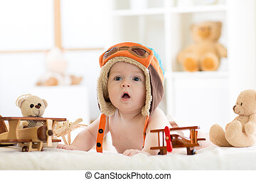 Funny baby boy weared pilot hat with wooden airplane and teddy bear toys