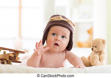 Funny baby boy weared pilot hat with wooden airplanes and teddy bear toys