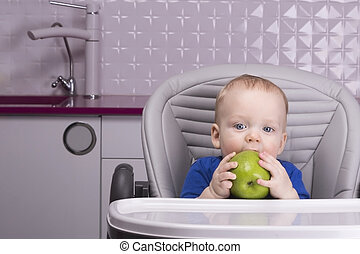 Funny baby boy with big green apple in the kitchen