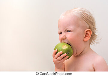 Funny baby eating apple