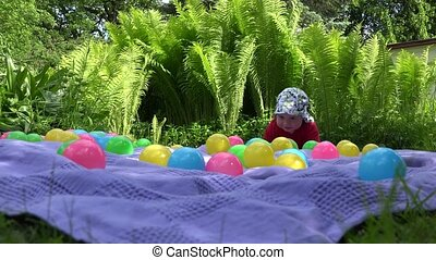 Funny baby girl crawl between colorful balls on plaid near fern plant. 4K