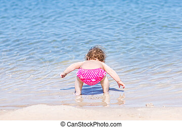 Funny baby girl drinking water on a beautiful beach