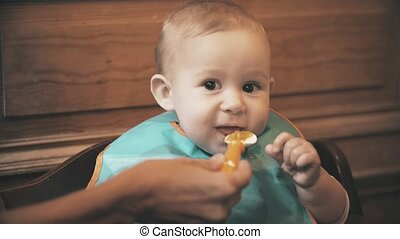 Funny baby girl eats unappetizing meal and frowns, close-up...