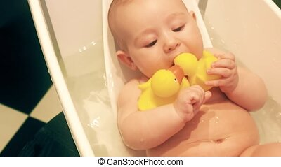 Funny baby girl holds rubber ducks in a bath tub - Funny...