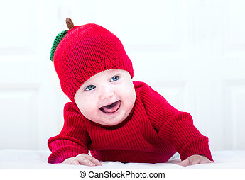 Funny baby girl in a knitted apple hat playing on her tummy