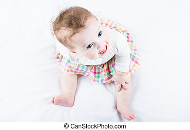 Funny baby girl in a plaid skirt sitting on a white blanket