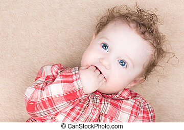 Funny baby girl in a red plaid shirt sucking on her finger