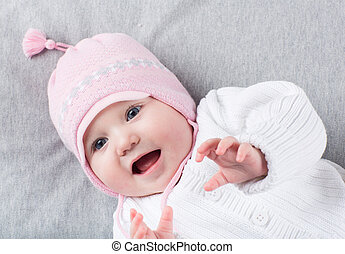 Funny baby girl in a warm knitted hat