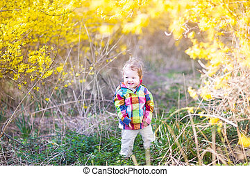 Funny baby girl playing in a colorful field