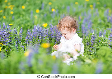 Funny baby girl playing in a garden