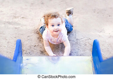 Funny baby girl playing on a slide