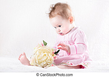 Funny baby girl playing with a big flower