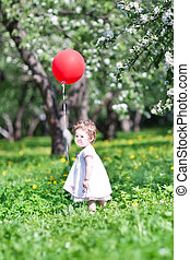 Funny baby girl playing with a big red balloon