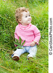 Funny baby girl playing with a snail in the garden
