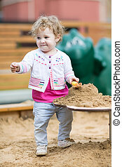 Funny baby girl playing with sand on a playground